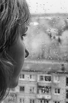 Ritratto di una donna premurosa dalla pelle bianca in piedi davanti alla finestra in un giorno di pioggia
