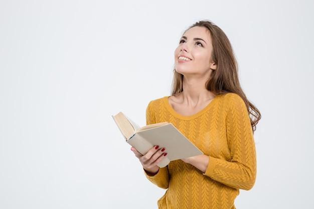 Ritratto di una donna premurosa che tiene in mano un libro e guarda il copyspace isolato su uno sfondo bianco