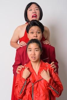 Ritratto di tre amici asiatici con diversità di età e personalità insieme contro il muro bianco