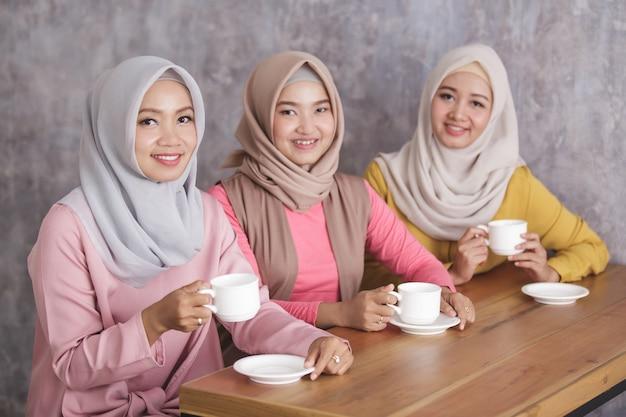 Un ritratto di tre belle donne musulmane che hanno un caffè insieme