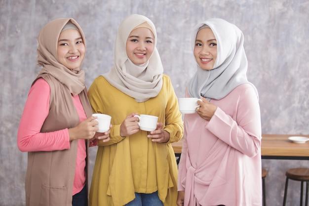 Ritratto di tre bella donna musulmana in piedi pur avendo un caffè insieme