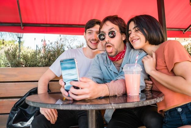Ritratto di tre amici che trascorrono del buon tempo insieme e prendendo un selfie con il telefono cellulare al bar. concetto di stile di vita e amicizia.