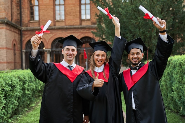 Ritratto di tre laureati felici che celebrano la laurea nel campus con diploma.