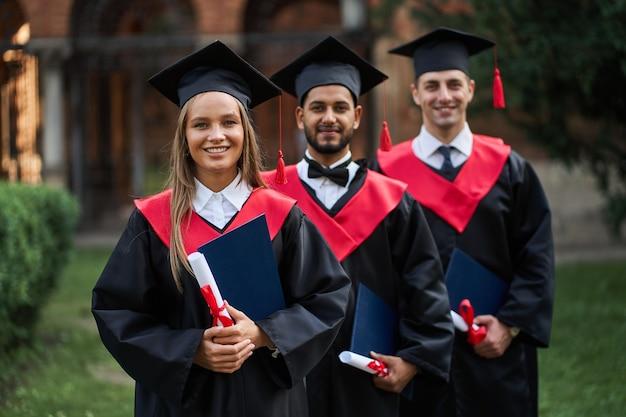 Un ritratto di tre laureati felici in abiti e diploma di graduazione.