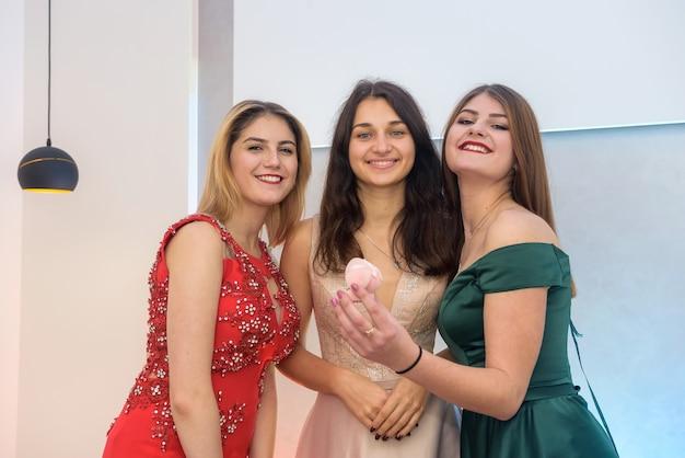 Ritratto di tre giovani donne felici, concetto di natale con confezione regalo e in abiti da sera alla festa