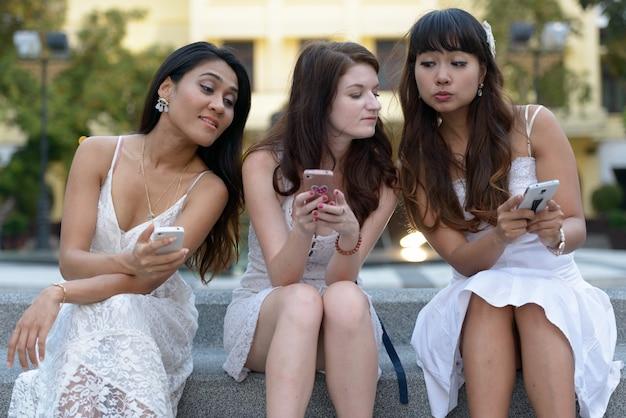 Ritratto di tre multietniche giovani belle donne come amici insieme al parco all'aperto