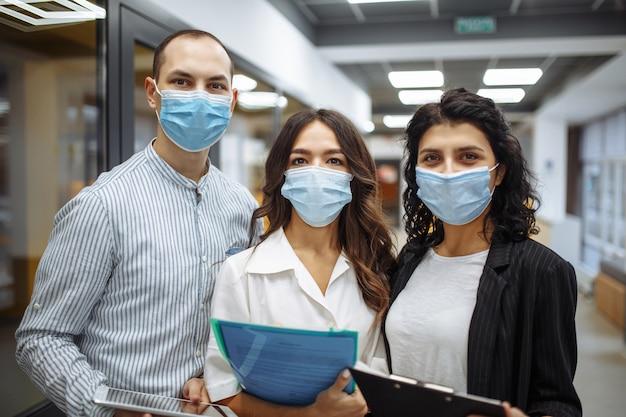 Ritratto di tre impiegati che indossano maschere mediche per discutere di affari e prospettive future.