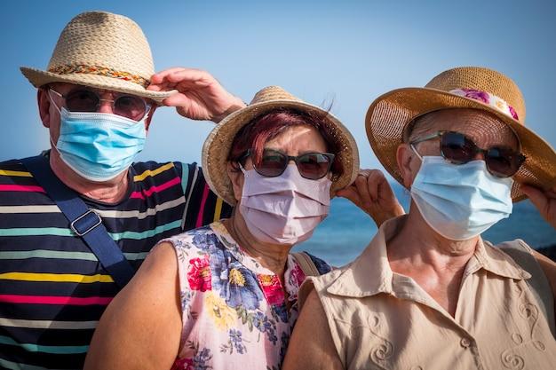 Ritratto di tre persone anziane in vacanza al mare che indossano una maschera medica