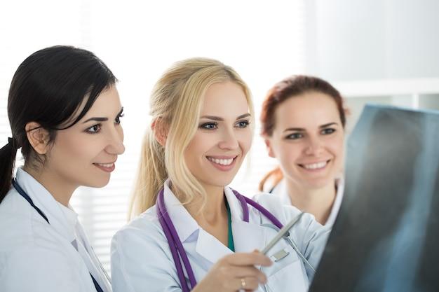 Un ritratto di tre medici femminili sorridenti della medicina che esaminano l'immagine dei raggi x. concetto di sanità e medicina.