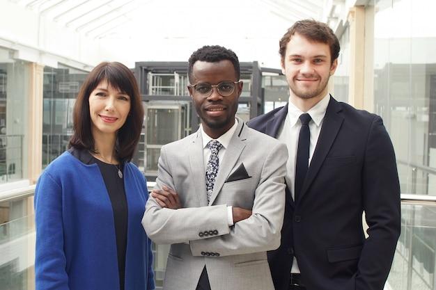 Un ritratto di tre persone di affari riuscite, gruppo di affari che posa nell'ufficio moderno