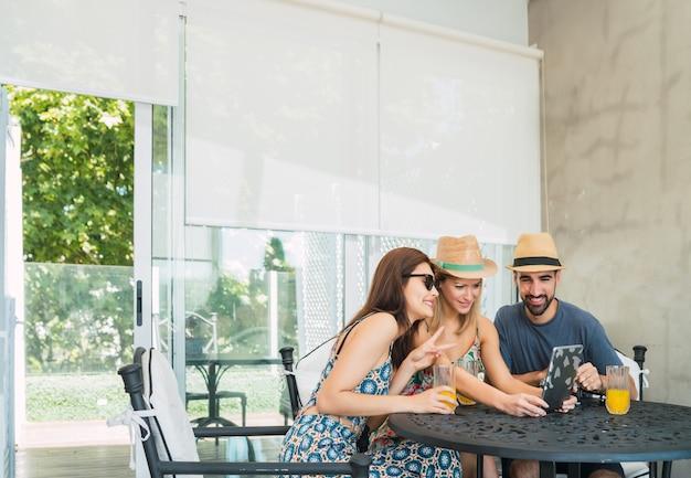 Ritratto di tre amici viaggiatori che trascorrono un po 'di tempo e utilizzano la tavoletta digitale in hotel