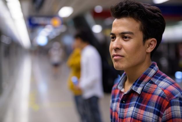 Un ritratto di tre giovani uomini asiatici dentro la stazione della metropolitana di bangkok, tailandia