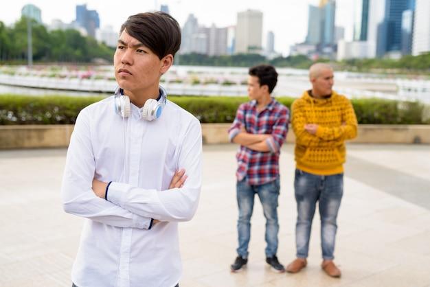 Un ritratto di tre giovani uomini asiatici che si rilassano insieme al parco a bangkok, tailandia