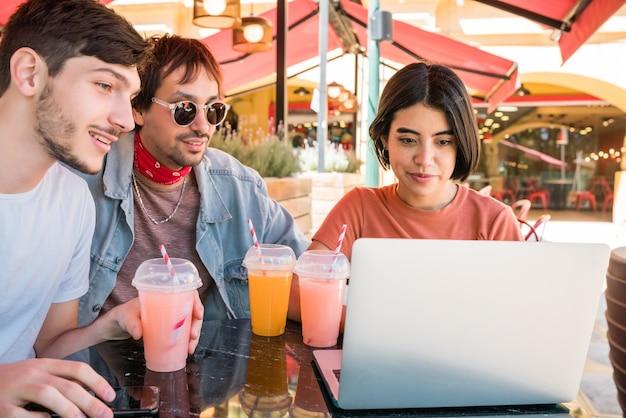 Ritratto di tre giovani amici utilizzando un computer portatile mentre è seduto all'aperto presso la caffetteria. amicizia e concetto di tecnologia.