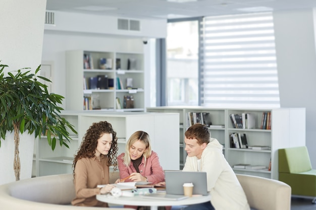 Ritratto di tre giovani che studiano insieme seduti a tavola nella biblioteca del college e lavorano su un progetto di gruppo,