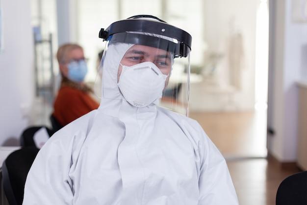 Ritratto di medico stanco in studio dentistico che guarda la telecamera indossando tuta e visiera seduto su una sedia nella clinica della sala d'attesa. concetto di nuova normale visita dal dentista nell'epidemia di coronavirus.