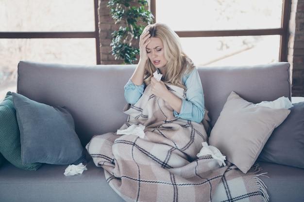 Ritratto di signora dai capelli ondulati malata esausta stanca che si siede sul divano sentendosi male
