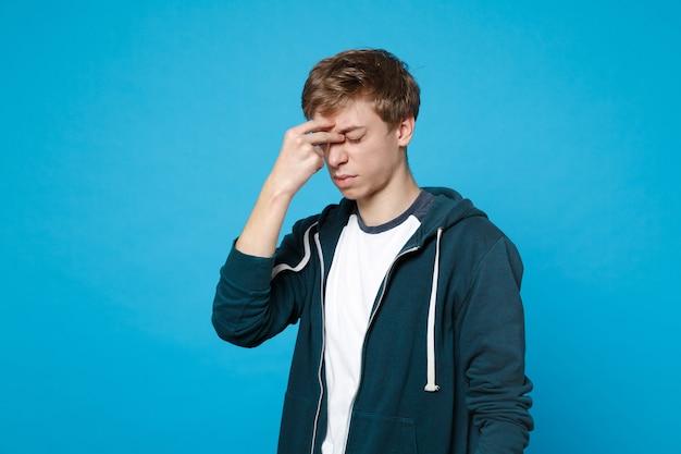 Ritratto di un giovane esausto stanco in abiti casual con gli occhi chiusi che mettono la mano sul viso isolato.