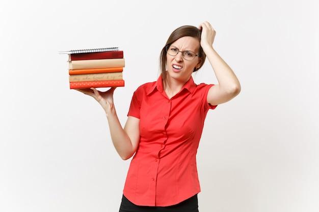 Ritratto della donna dell'insegnante di affari turbata frustrata stanca in bicchieri di camicia rossa che tengono libri di testo della pila in mani isolate su fondo bianco. istruzione o insegnamento nel concetto di università delle scuole superiori.