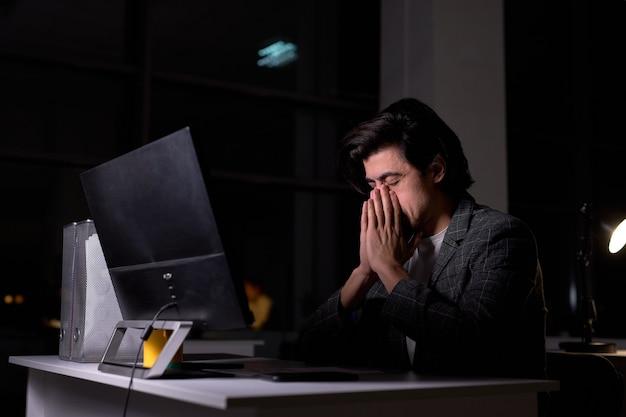 Ritratto di uomo stanco in abito seduto alla scrivania in ufficio utilizzando il computer pc, pensando, avendo un compito difficile, non c'è tempo per dormire. vista laterale su un ragazzo bruno di aspetto caucasico, lavoro sul progetto
