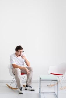 Ritratto di un uomo stanco, stressato e con mal di testa, con in mano un bicchiere d'acqua