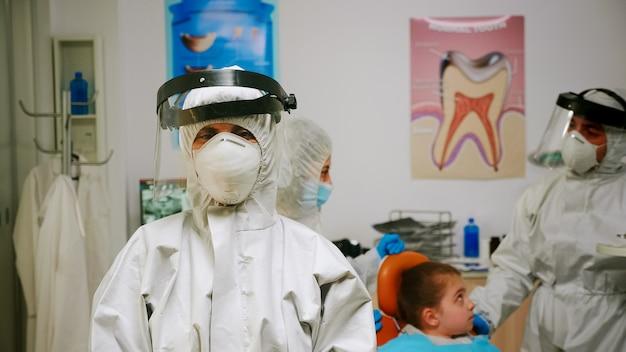 Ritratto di una donna stomatologa stanca con tuta e visiera che guarda l'obbiettivo seduto nel nuovo normale studio dentistico. infermiera pediatrica che parla con un bambino paziente in background.