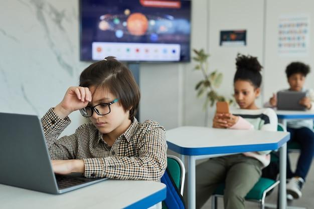 Ritratto di un adolescente stanco che utilizza il computer portatile mentre è seduto alla scrivania in aula scolastica, copia spazio
