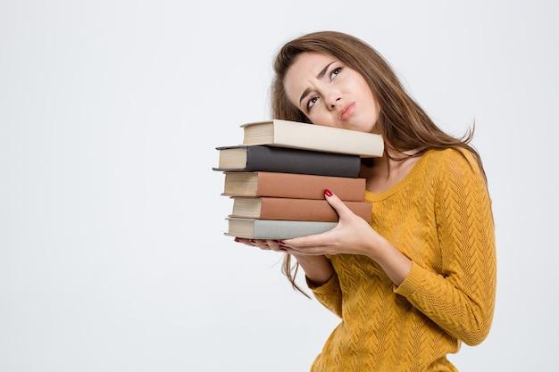 Ritratto di una donna stanca con libri isolati su sfondo bianco white