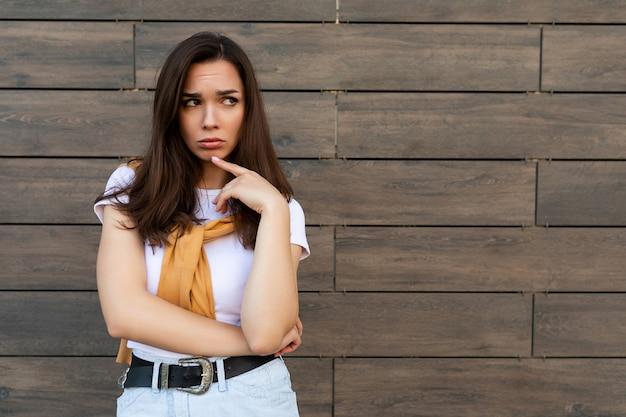 Ritratto di una giovane donna brunetta risentita e triste, sconvolta e irritata, che indossa una maglietta bianca casual
