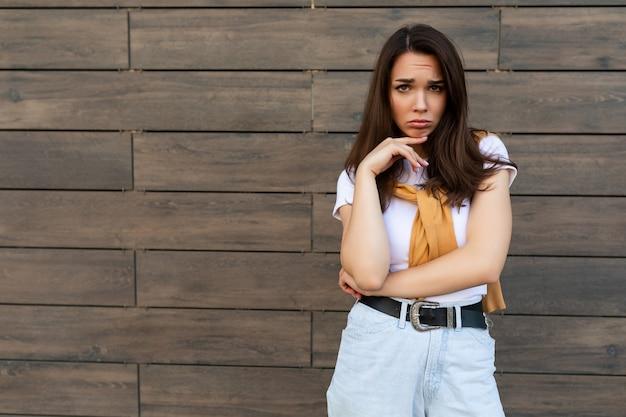 Ritratto di una giovane donna bruna offesa, triste e permalosa che indossa una maglietta bianca casual