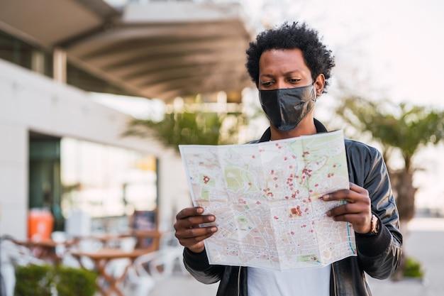 Ritratto di uomo turistico che indossa una maschera protettiva e cerca indicazioni sulla mappa mentre si cammina all'aperto per strada