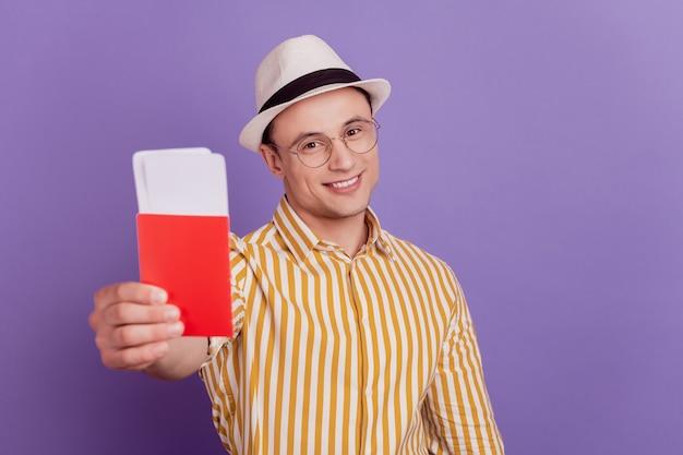 Il ritratto del ragazzo positivo turistico tiene il passaporto dei biglietti dimostra opportunità di viaggio su sfondo viola