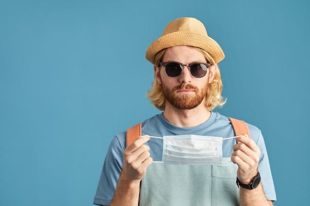 Ritratto di turista in occhiali da sole e in cappello che indossa la maschera protettiva isolata su sfondo blu