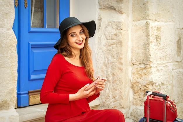 Ritratto di turista giovane donna caucasica in un abito lungo rosso e cappello nero con valigia