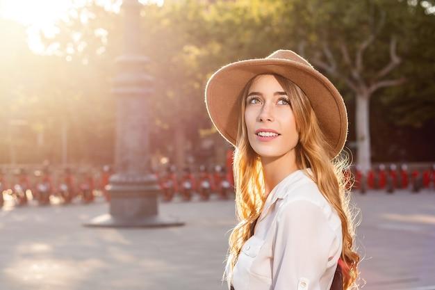 Ritratto di una donna viaggiatore che indossa un cappello fedora in città