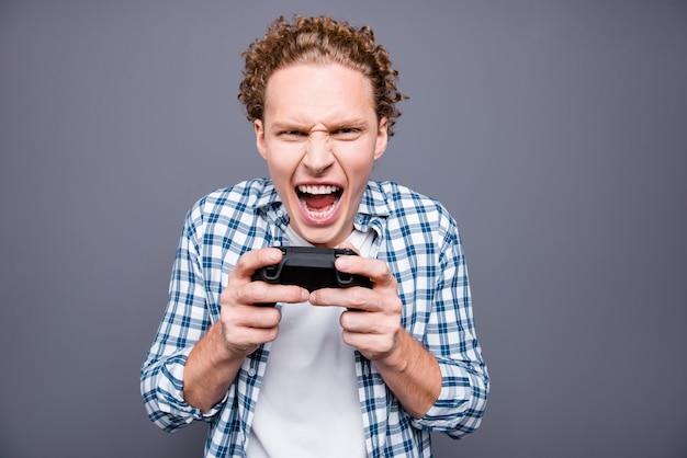 Ritratto del tossicodipendente alla moda uomo pazzo che gioca video gioco nella stazione