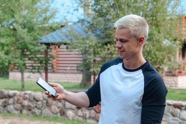 Ritratto di giovane uomo d'affari carino alla moda con telefono in campagna all'aperto. uomo attraente in vestiti casuali domestici che camminano nel paese rurale. ispirazione creativa e attività di avvio. copia spazio