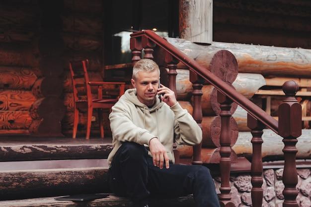Ritratto di giovane uomo d'affari alla moda che chiama sulla terrazza esterna del telefono della casa di campagna. uomo maniaco del lavoro in abiti casual domestici che lavorano in zone rurali. ispirazione creativa e attività di avvio. copia spazio