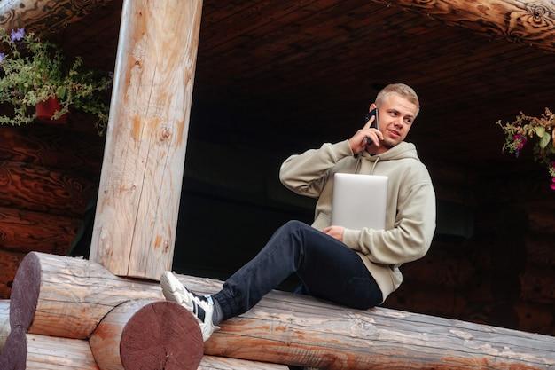 Ritratto di giovane uomo d'affari alla moda con il terrazzo all'aperto del computer portatile della casa di campagna. uomo maniaco del lavoro in abiti casual da casa che chiama al telefono. ispirazione creativa e attività di avvio. copia spazio