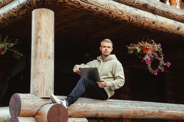 Ritratto di giovane uomo d'affari alla moda con il terrazzo all'aperto del computer portatile della casa di campagna. uomo maniaco del lavoro in abiti casual domestici che lavorano in vacanza. ispirazione creativa e start-up. copia spazio