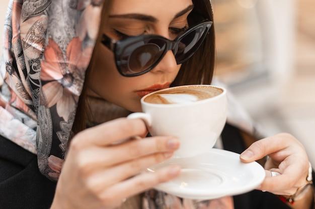 Ritratto alla moda giovane donna lussuosa in scialle di seta alla moda sulla testa in eleganti occhiali da sole scuri con una tazza bianca vintage con caffè. la ragazza attraente del modello di moda beve il cappuccino caldo. avvicinamento.