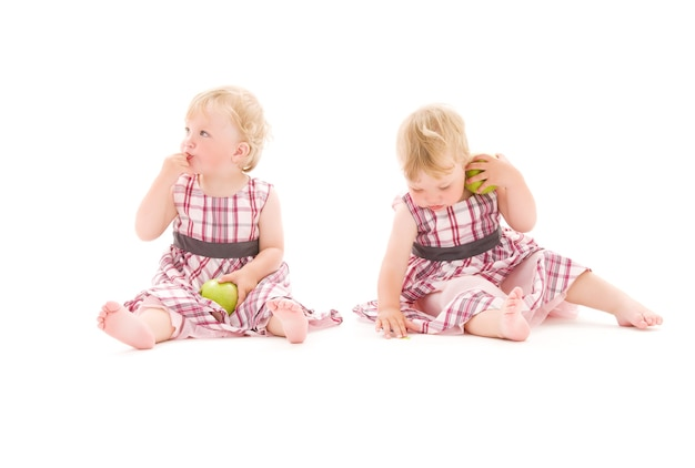 Ritratto di due adorabili gemelli sul muro bianco