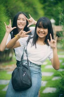 Un ritratto di due adolescenti asiatici che si distendono con la felicità nel parco verde