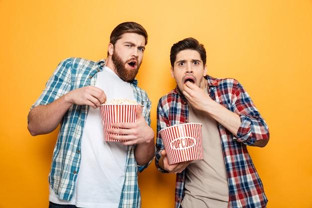 Ritratto di due giovani stupiti che mangiano popcorn