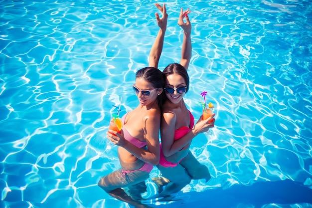 Ritratto di due ragazze attraenti che bevono cocktail in piscina