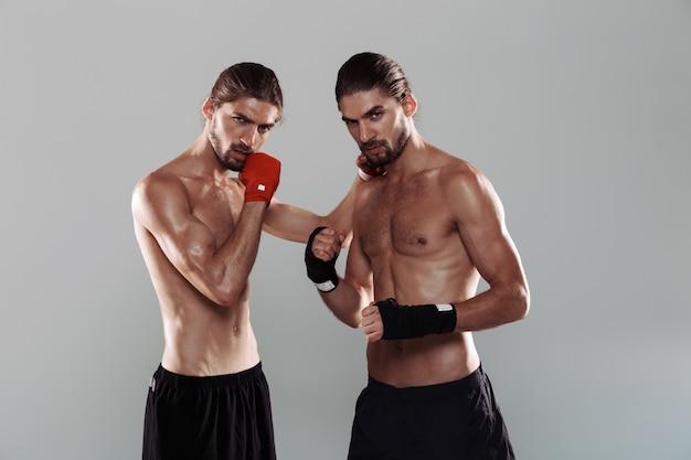 Ritratto di due fratelli gemelli senza camicia muscolosi attraenti