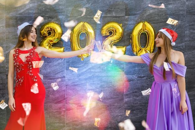 Ritratto di due belle ragazze alla vigilia di capodanno che indossano eleganti abiti da sera