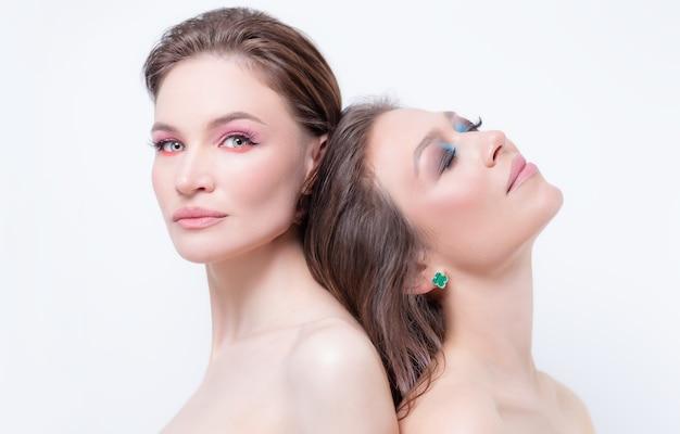 Ritratto di due belle ragazze con trucco provocatorio su sfondo bianco. concetto di amicizia femminile. alta qualità