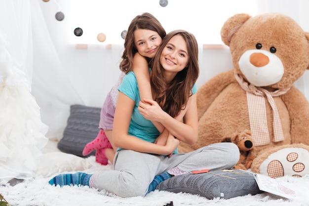 Ritratto di due belle sorelle sorridenti sedute insieme nella stanza dei bambini