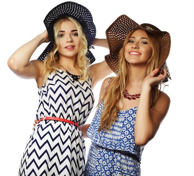 Ritratto di due migliori amiche ragazze che indossano eleganti abiti estivi e cappelli di paglia, che si divertono insieme. isolato su bianco.